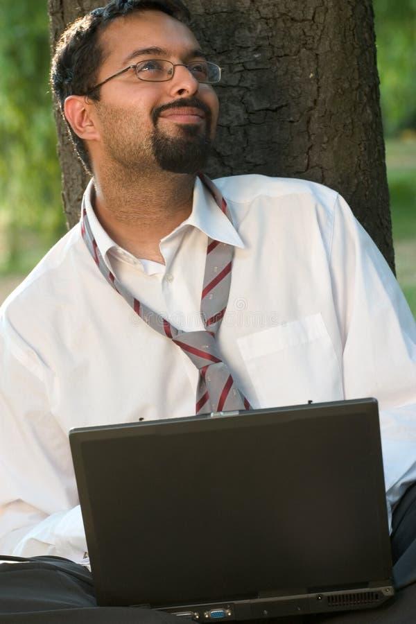 Indio con una sonrisa de la computadora portátil foto de archivo