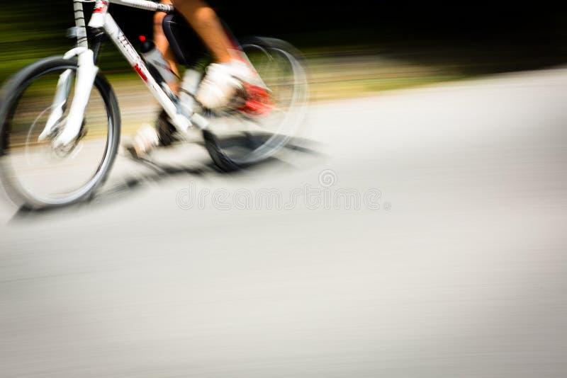 Indique al ciclista borroso que va rápidamente en un carril de la bici de la ciudad imagen de archivo libre de regalías