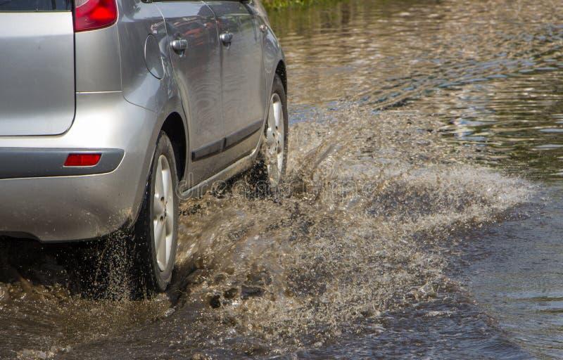 Indique a lluvia del coche el charco grande del espray de agua de las ruedas imágenes de archivo libres de regalías