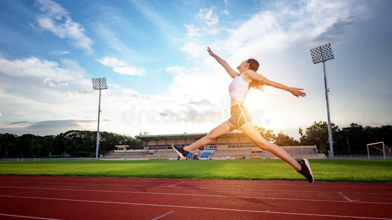 Indique los ejercicios asiáticos de la mujer joven con el funcionamiento y el salto imágenes de archivo libres de regalías