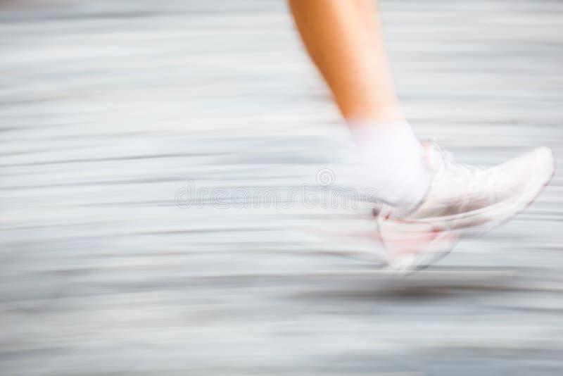 Indique los pies del corredor borroso en un ambiente de la ciudad imagen de archivo