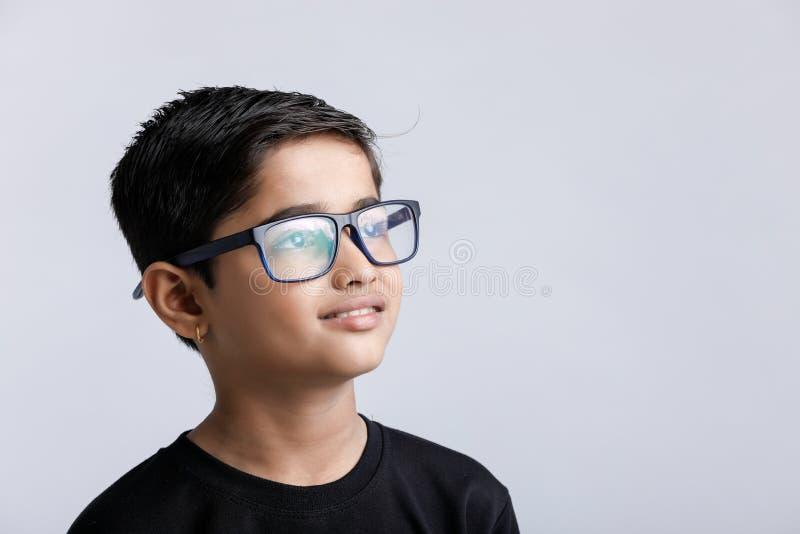 Indisch kind die die bril dragen over witte achtergrond wordt geïsoleerd royalty-vrije stock afbeelding