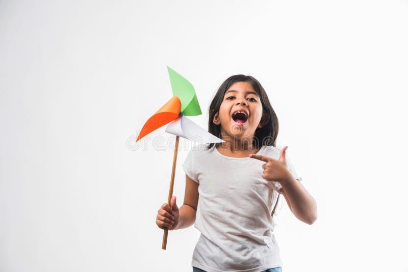 Indisch klein die meisje en tricolour windmolen van de gezichtsholding uit saffraan, groen en wit kleurendocument, gelukkige onaf royalty-vrije stock afbeelding
