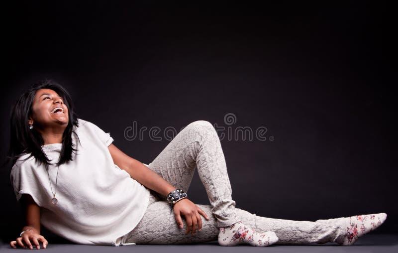 Indisch meisje die op de vloer lachen royalty-vrije stock foto's