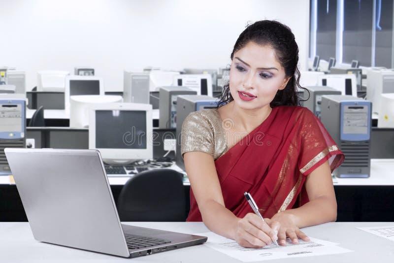Indisch onderneemster het schrijven document in bureau stock fotografie