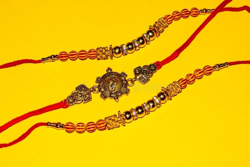 Indisch traditioneel festival Raksha Bandhan, Elegante Rakhi over gele achtergrond royalty-vrije stock afbeelding