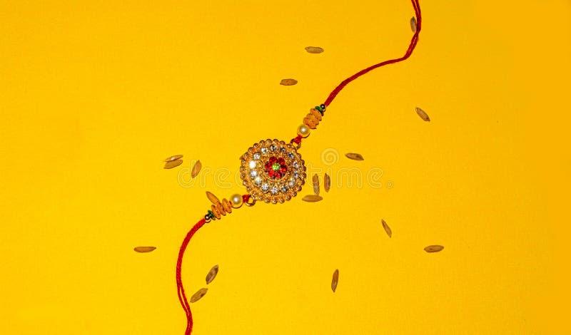 Indisch traditioneel festival Raksha Bandhan, Elegante Rakhi over gele achtergrond royalty-vrije stock afbeeldingen
