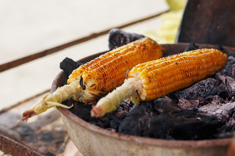 Indisch voedsel op het strand - de verse maïskolven worden geroosterd op de steenkolen Strand bij GOA-Zonsondergang royalty-vrije stock fotografie