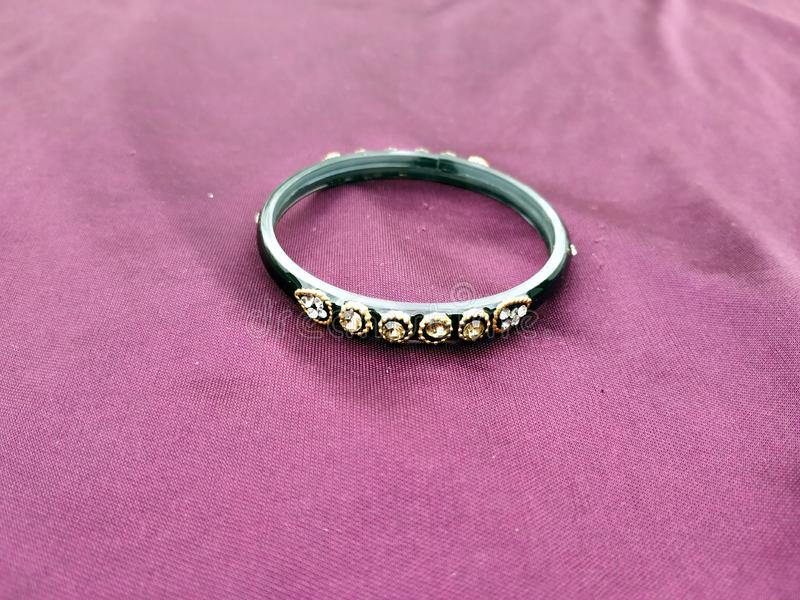 Indische Armb?nder Armband mit Diamanten auf violettem Hintergrund lizenzfreie stockfotos