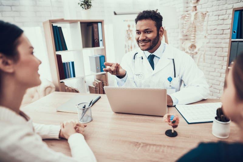 Indische arts die patiënten in bureau zien De arts gebruikt laptop bij lijst royalty-vrije stock foto's
