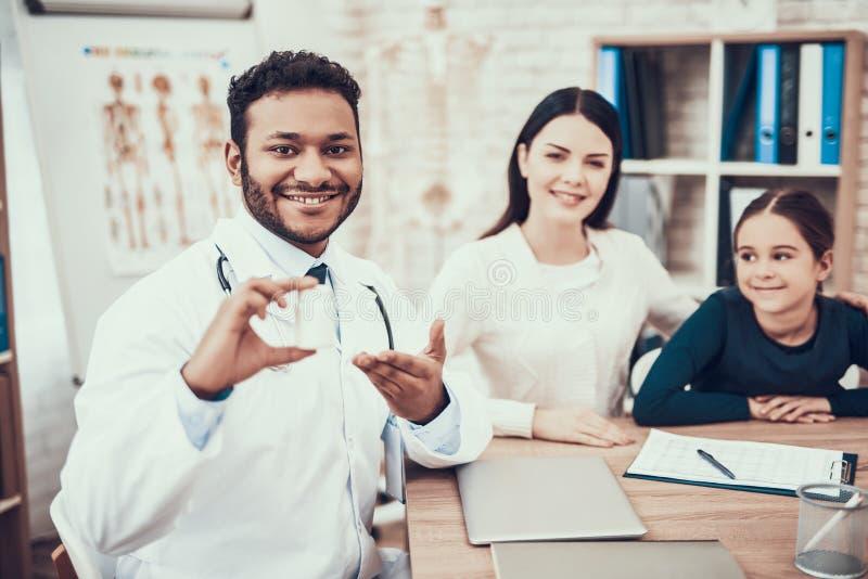 Indische arts die patiënten in bureau zien De arts geeft moeder en dochterfles van pillen stock foto