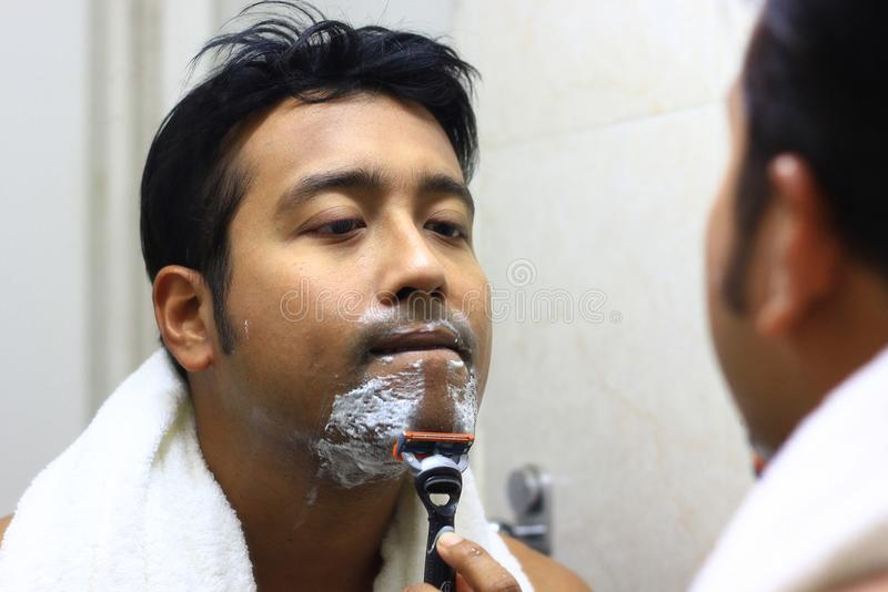 Indische Aziatische mens die voor zijn verschijning voor een spiegelschoonheid het stileren levensstijl zorgen Het scheren routin stock fotografie