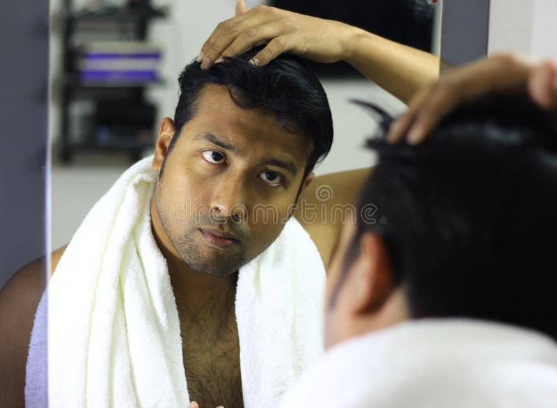 Indische Aziatische mens die voor zijn verschijning voor een spiegelschoonheid het stileren levensstijl zorgen Stilerend Haar stock foto's