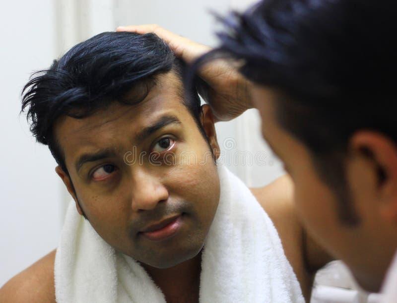 Indische Aziatische mens die voor zijn verschijning voor een spiegelschoonheid het stileren levensstijl zorgen Stilerend Haar stock afbeelding