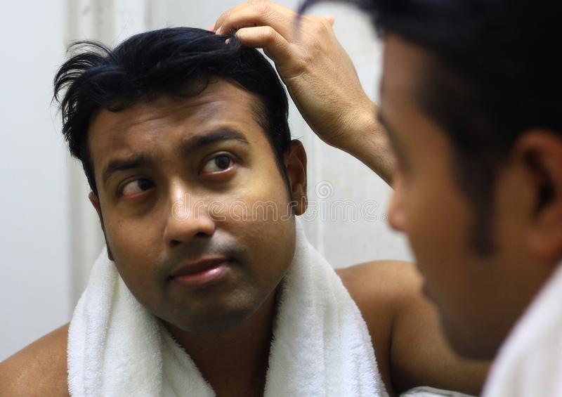 Indische Aziatische mens die voor zijn verschijning voor een spiegelschoonheid het stileren levensstijl zorgen Stilerend Haar royalty-vrije stock afbeelding