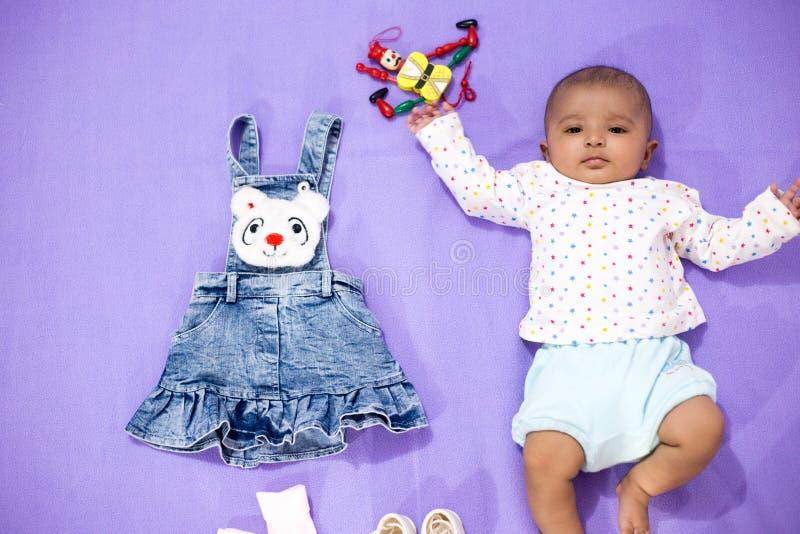 Indische baby met kleren en speelgoed stock afbeeldingen