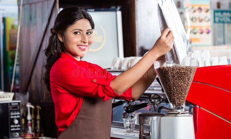 Indische barista vullende koffiemolen stock afbeelding