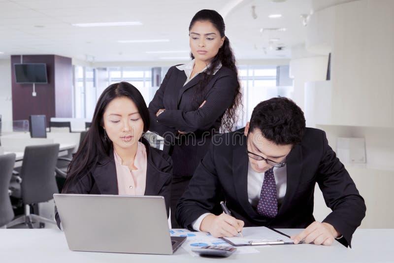 Indische bedrijfsleider die over haar personeel letten op stock foto's