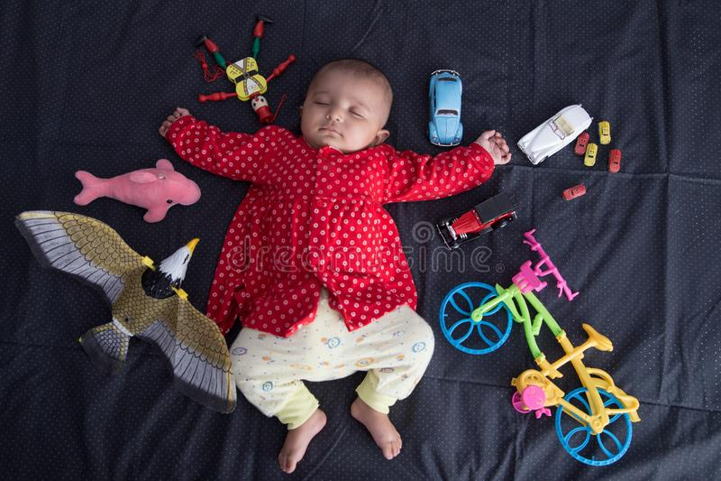 Indische de slaapslaap van de Zuigelingsbaby met speelgoed stock foto