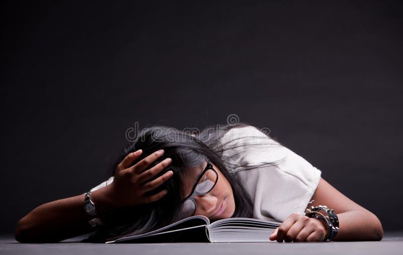 Indische die meisjesslaap van het bestuderen wordt vermoeid stock afbeeldingen