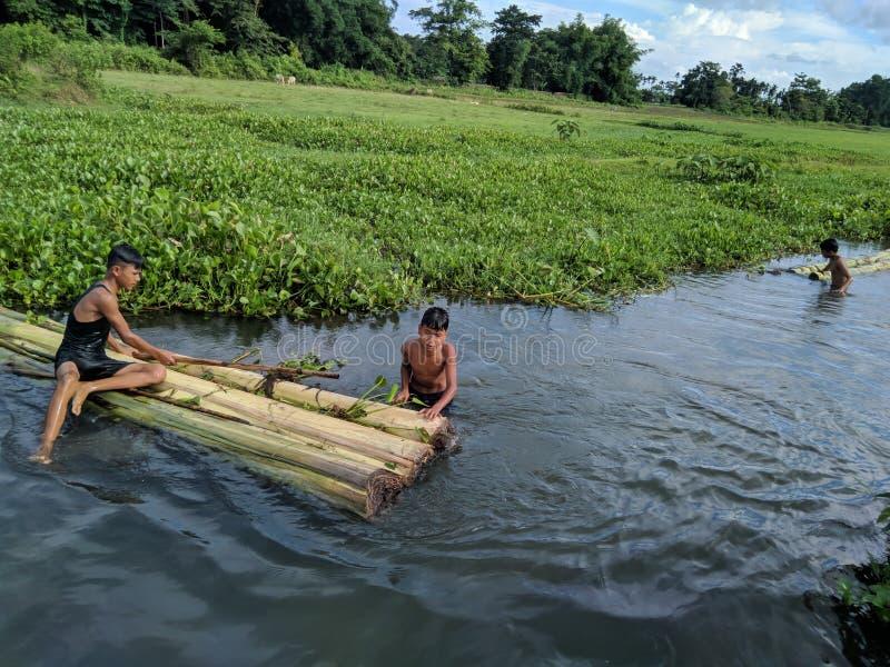 Indische Dorfkinder, die mit ihrem handgemachten Bananenboot auf der Sommerzeit bei Tinsukia, Assam, Indien am 21. Juni 2019 geni stockfoto