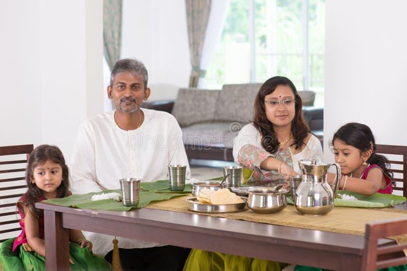 Indische familie die thuis dineren stock foto's