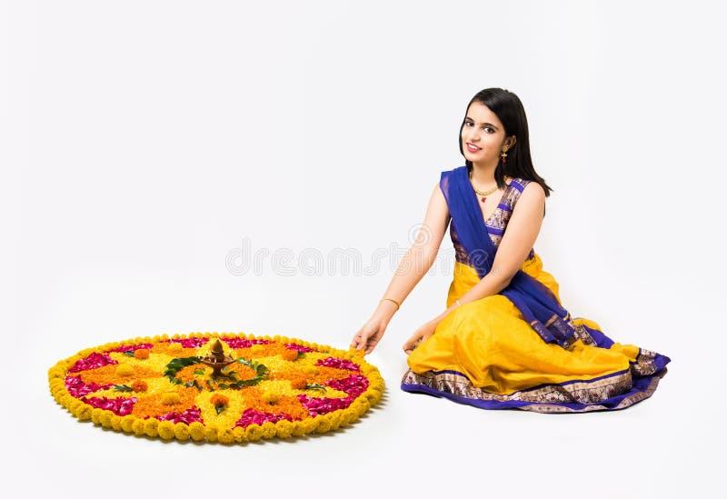 Indische Frau, die rangoli unter Verwendung der Blumen macht stockbilder
