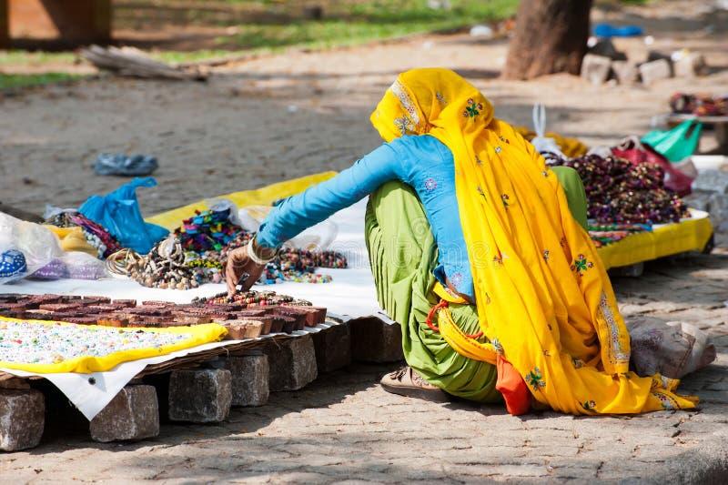 Indische Frau im bunten Sari verkauft Andenken stockbild