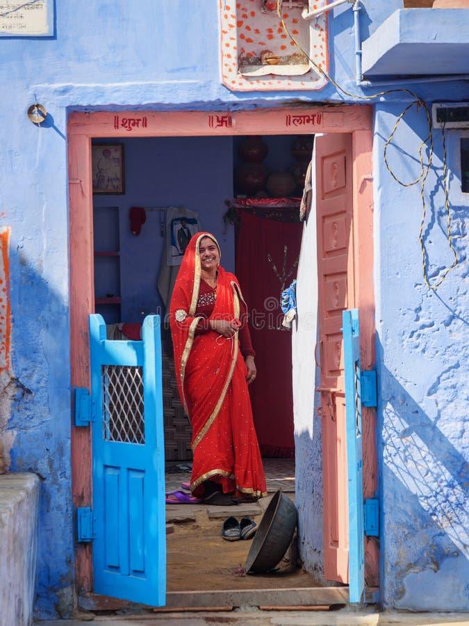 Indische Frau im roten Sari in der Tür des blauen Hauses im Sambhar See-Dorf Rajasthan Indien lizenzfreies stockfoto