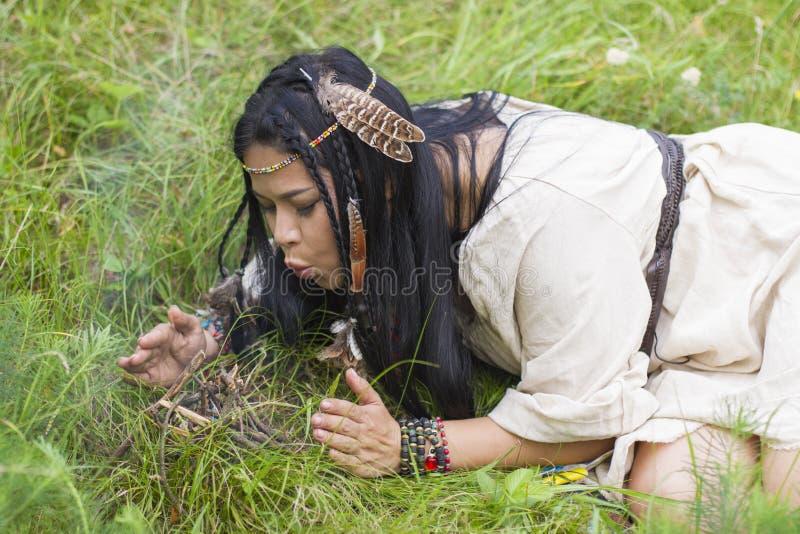 Indische Frau macht ein Feuer auf Gras stockfoto