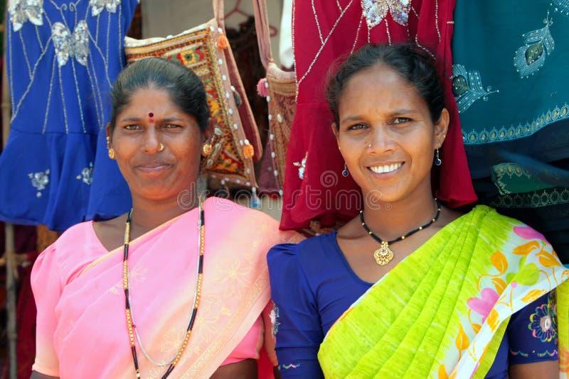 Indische Frauen in den bunten Sari, die Kleidung auf dem Strand verkaufen stockbild