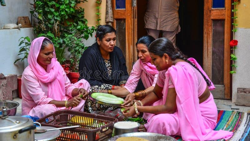 Indische Frauen, die traditionelles Lebensmittel kochen stockfotografie