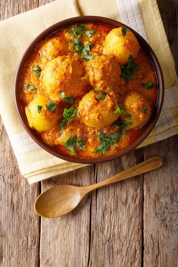 Indische gebraden aloo van aardappelsdum in het close-up van de kerriesaus verticaal royalty-vrije stock afbeelding