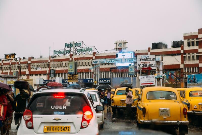 Indische gelbe Taxis und andere Autos, die in den Regen mit Regenschirm nahe dem Bereich des Bahnhofs Howrah-Kreuzung warten stockfotografie