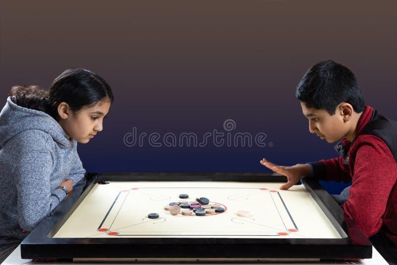 Indische Geschwister, die Carrom auf dem Carrom-Brett spielen lizenzfreie stockbilder