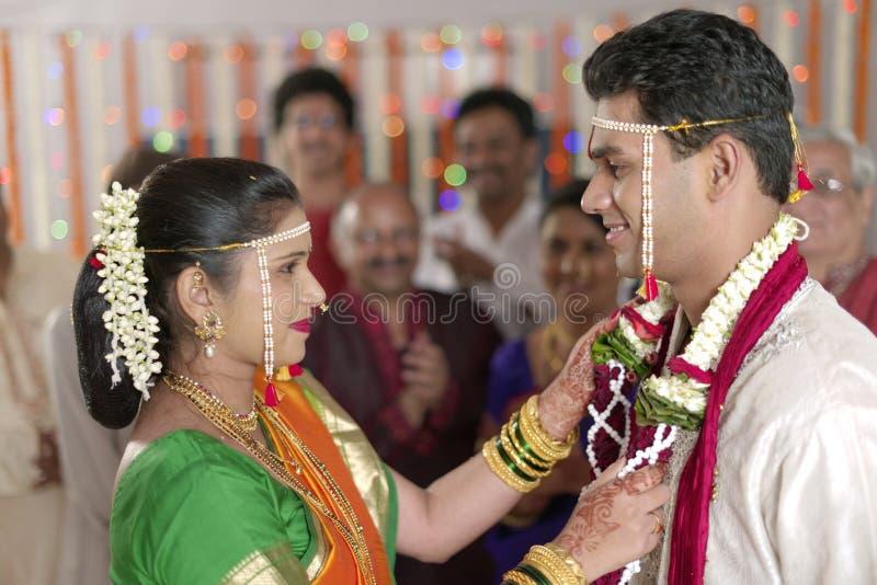 Indische hindische Braut, die Bräutigam betrachtet und Girlande in der Maharashtrahochzeit austauscht lizenzfreies stockbild