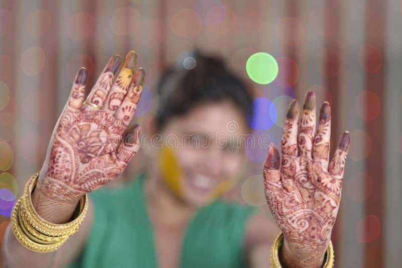 Indische hindische Braut, die Hennastrauch auf ihren Palmen zeigt. stockfoto