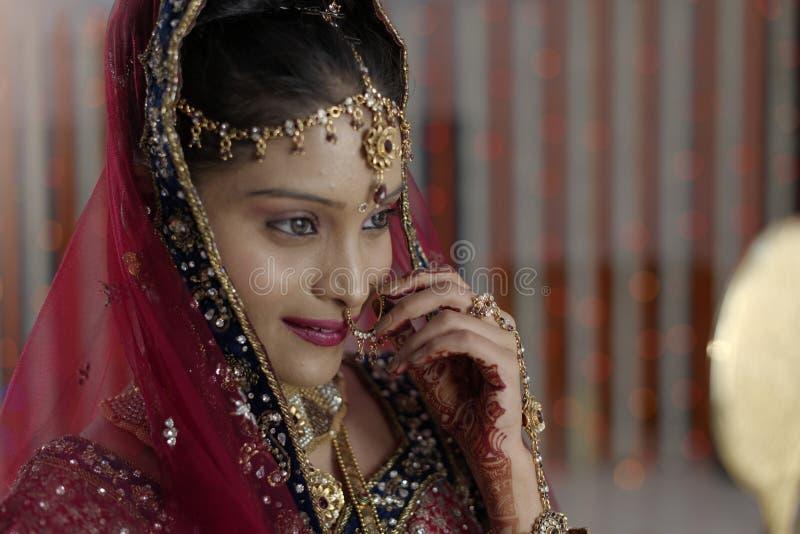 Indische hindische Braut mit dem Schmuck, der im Spiegel schaut. stockbild