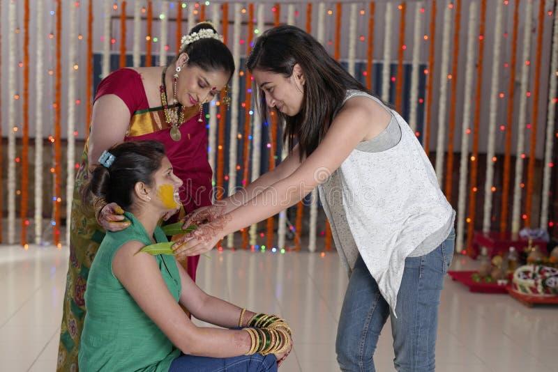 Indische hindische Braut mit Gelbwurzpaste auf Gesicht mit Schwester und Mutter. stockfoto