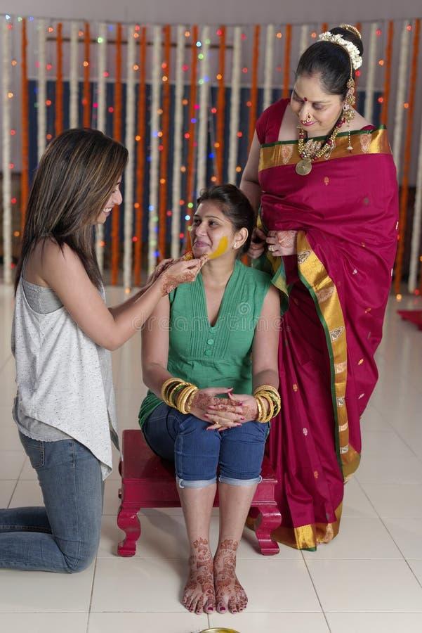 Indische hindische Braut mit Gelbwurzpaste auf Gesicht mit Schwester und Mutter. lizenzfreies stockfoto