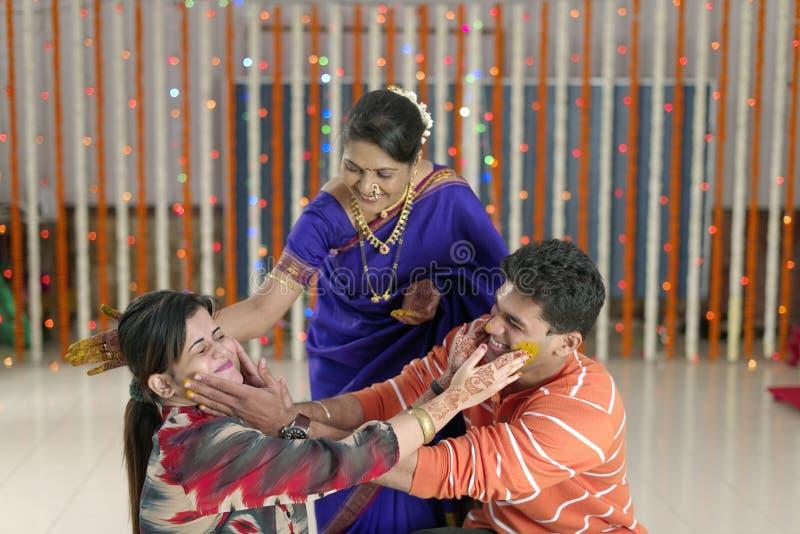 Indische Hindoese bruidegom met kurkumadeeg op gezicht met moeder royalty-vrije stock foto's