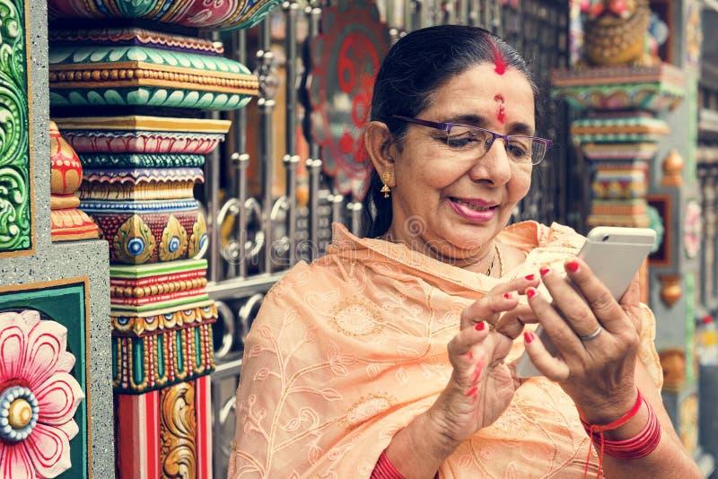 Indische hogere vrouw die mobiele telefoon met behulp van stock fotografie