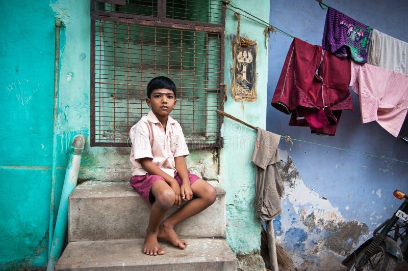Indische jongenszitting dichtbij kleurrijke muur van zijn huis bij straat royalty-vrije stock foto