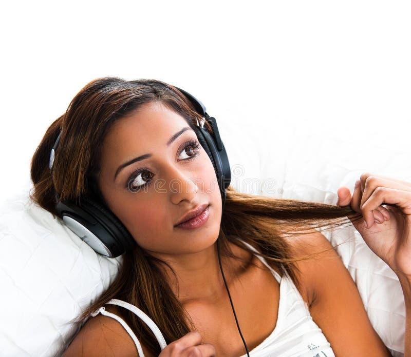 Indische Jugendliche, wenn die Kopfhörer Haar anhalten lizenzfreie stockfotos