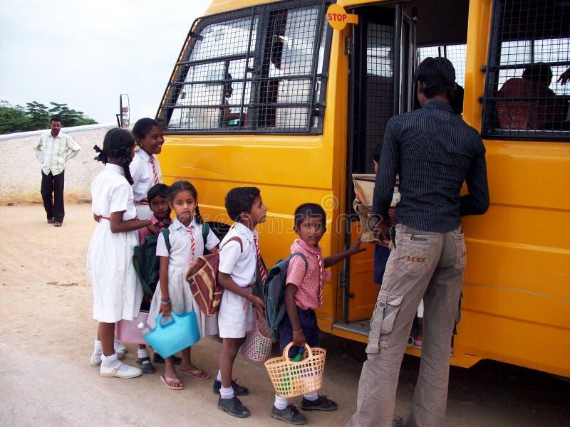 Indische Kinder, die in Schulbus einsteigen lizenzfreie stockfotos