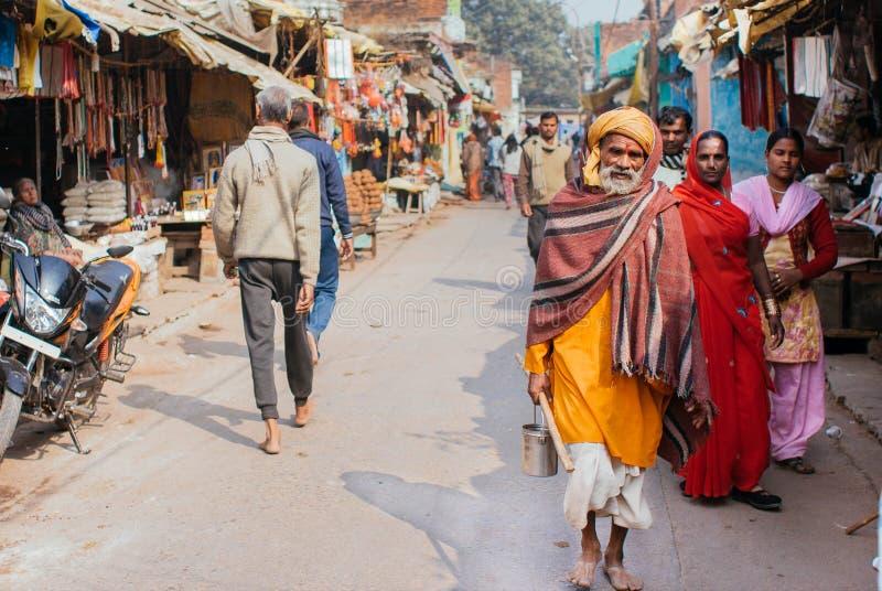 Indische Leute, die auf Marktstraße mit Speichern und Geschäften in der kleinen Stadt gehen stockbilder