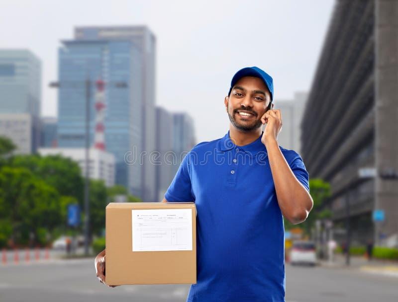 Indische leveringsmens met smartphone en pakketdoos stock foto