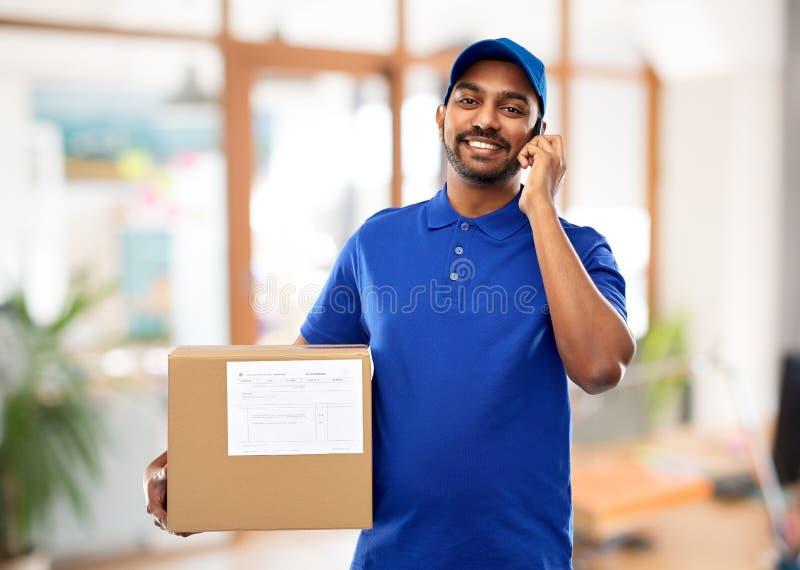 Indische leveringsmens met smartphone en pakketdoos royalty-vrije stock afbeeldingen