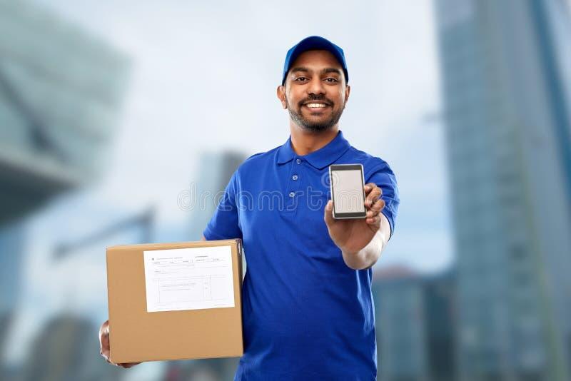 Indische leveringsmens met smartphone en pakketdoos stock foto's