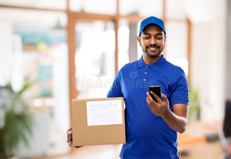 Indische leveringsmens met smartphone en pakketdoos royalty-vrije stock foto's